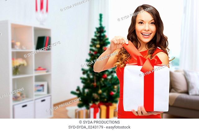 smiling woman with christmas gift at home