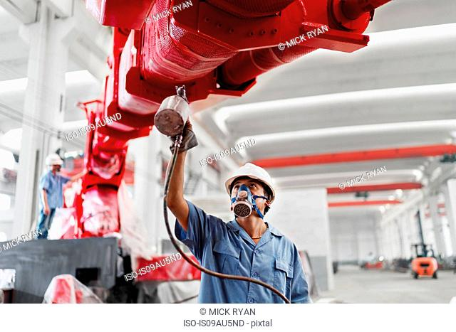 Male workers spray painting a crane arm red in factory workshop, China