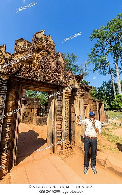 Park guide near red sandstone entrance at Banteay Srei Temple in Angkor, Siem Reap Province, Cambodia, Khmer