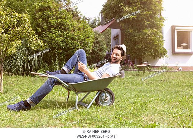 Smiling man lying in wheelbarrow in garden