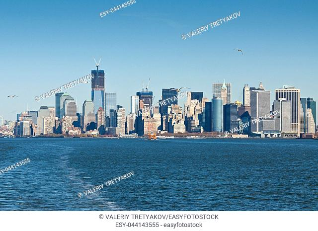 A panoramic view of the Manhattan skyline in New York City. The foreground of the picture is the Hudson River