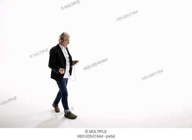 Businessman listening to music with headphones and mp3 player against white background