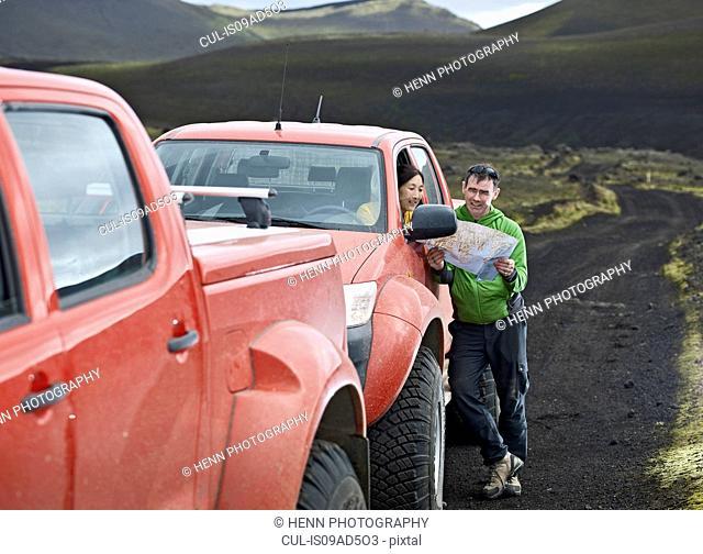 Couple reading map by customised SUV, Hekla, Fjallabak, Iceland