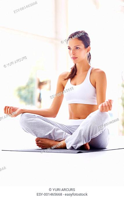 Portrait of healthy young woman practicing yoga on exercising mat