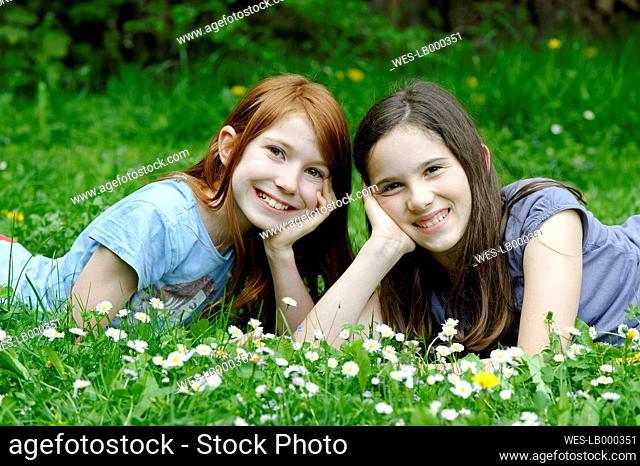 Girls are lying in a flower meadow