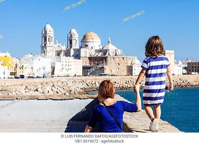 Tourists mother and daughter with blue striped t shirt on the promenade with the Cathedral of Cadiz, Andalusia, Spain