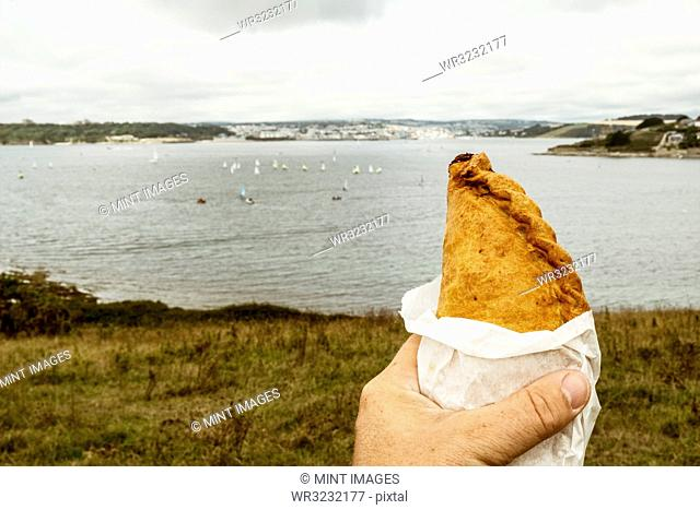 A hand holding a Cornish pasty baked pastry with a crimped edge, seated overlooking a sea estuary