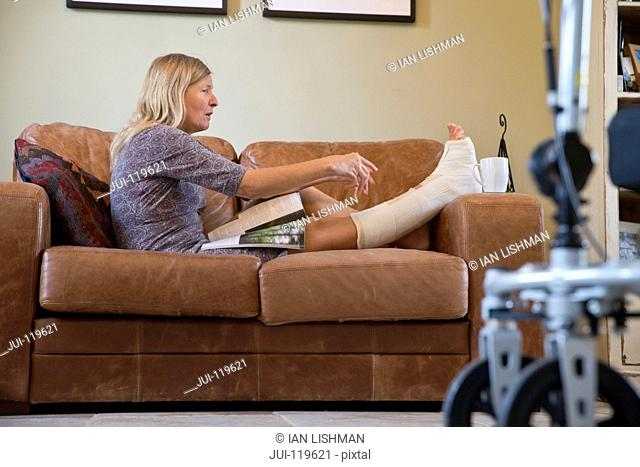 Mature Woman With Leg In Plaster Cast Lying On Sofa At Home Reaching For Cup