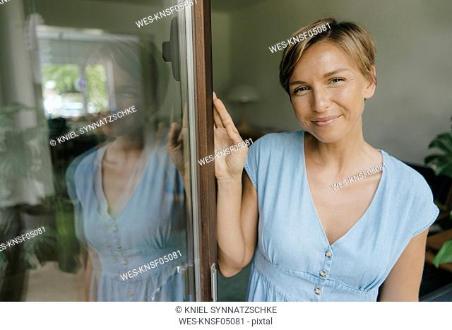 Portrait of smiling woman at French window
