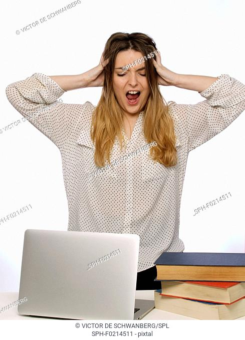 Woman with hands in hair and laptop