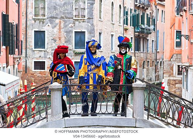 Masked persons on a bridge at the carnival in Venice, Italy, Europe