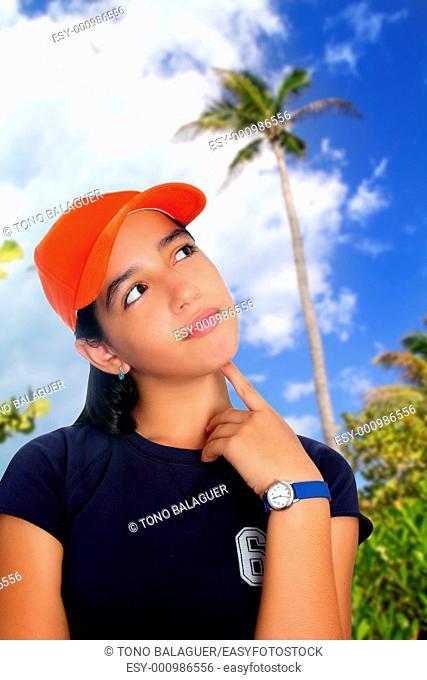 Latin teen hispanic pensive girl orange cap in palm tree jungle vacation