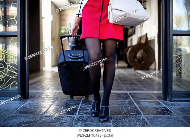 Legs of woman pulling suitcase out of building front door