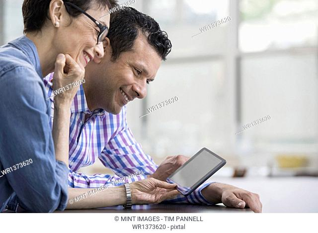 Professionals in the office. A light and airy place of work. Two people sitting at a desk, using a digital tablet. Work colleagues