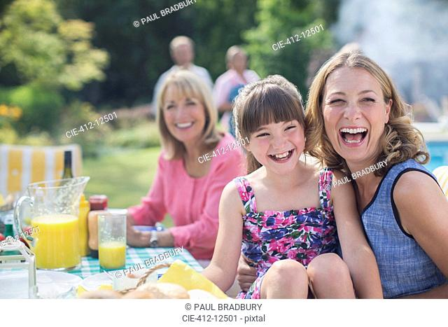 Multi-generation family laughing at table in backyard