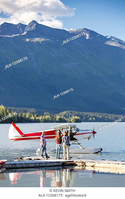 Visitors wait for the pilot to dock while, Trail Lake Float Plane Base, Moose Pass, Kenai Peninsula, Southcentral Alaska, USA