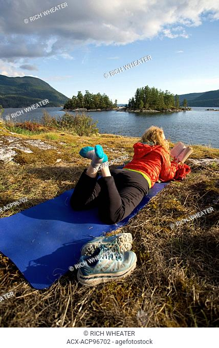 Woman reading book on yoga mat while camping at Kunechin Point, Sechelt Inlet. Gibsons, Sunshine Coast, British Columbia, Canada