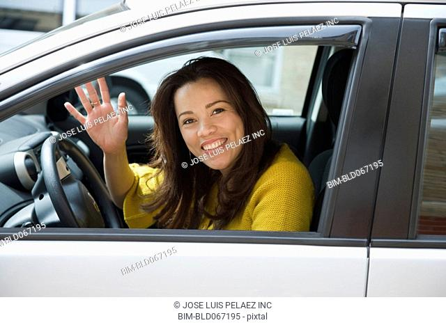 Hispanic woman driving and waving