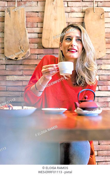 Smiling woman drinking tea in a cafe