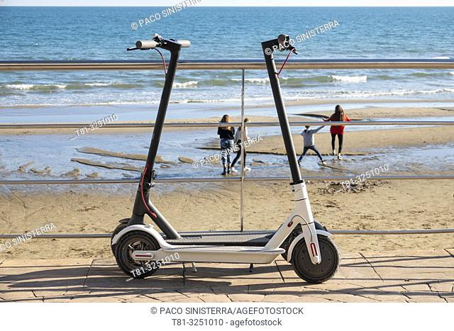 Electric scooters and people in background. Beach of Castellon. Valencian Community. Spain