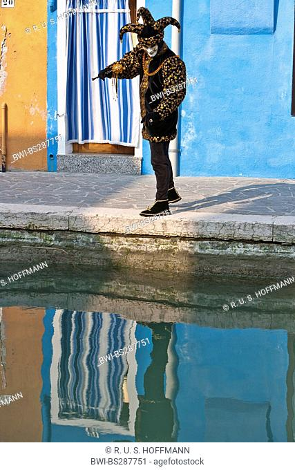 disguised man at carnival in venice looking at his reflection in a chanel, Germany, Venice, Burano