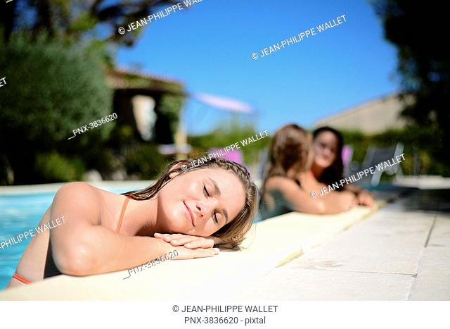 Portrait of a beautiful young woman eyes shut sunbathing by the poolside of a resort swimming pool during summer holiday