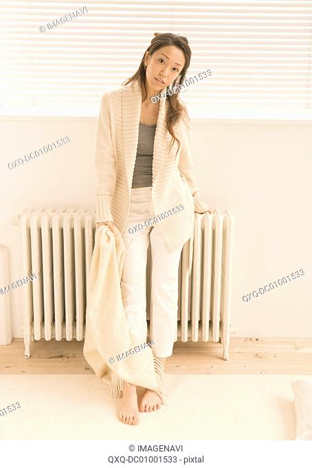 Woman leaning against heater
