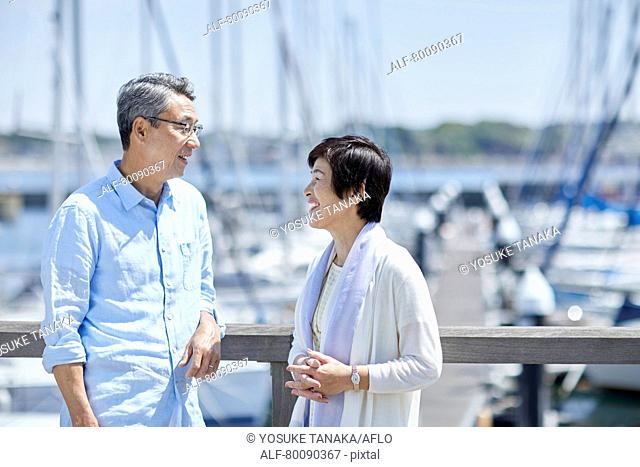 Japanese senior couple having fun by the sea