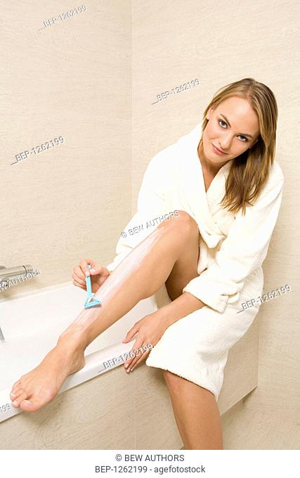 Young woman shaving her legs