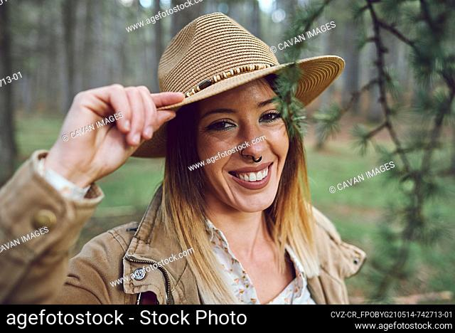 Woman on the mountain. She is in a forest with pine trees