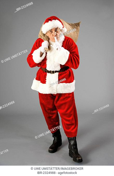 Santa Claus covering his mouth with an index finger, silence
