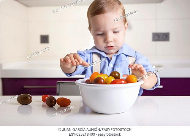 Baby boy playing with ripe colorful cherry tomatoes. Education on healthy nutrition for children concept