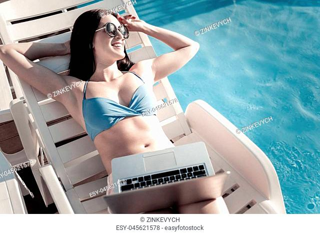 Vacation is calling. Radiant millennial girl wearing sunglasses looking into vacancy with a cheerful smile on her face while sunbathing with a laptop on her...