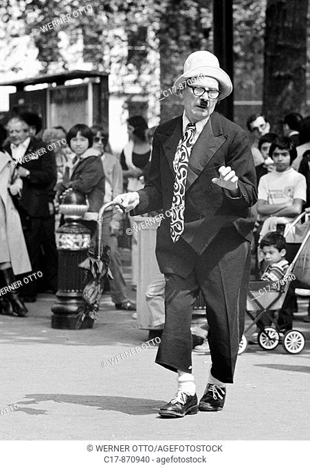 Seventies, black and white photo, humour, people, visitors on a sqare have fun with a costumed comedian, aged 60 to 70 years, Great Britain, England, London