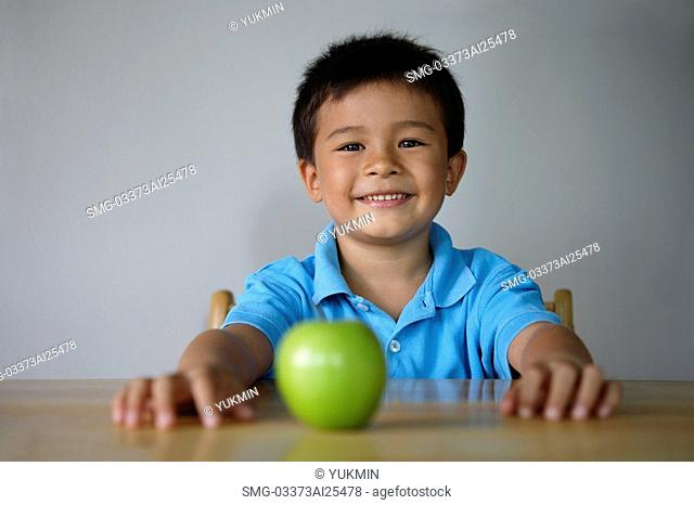 Boy sitting at table with green apple