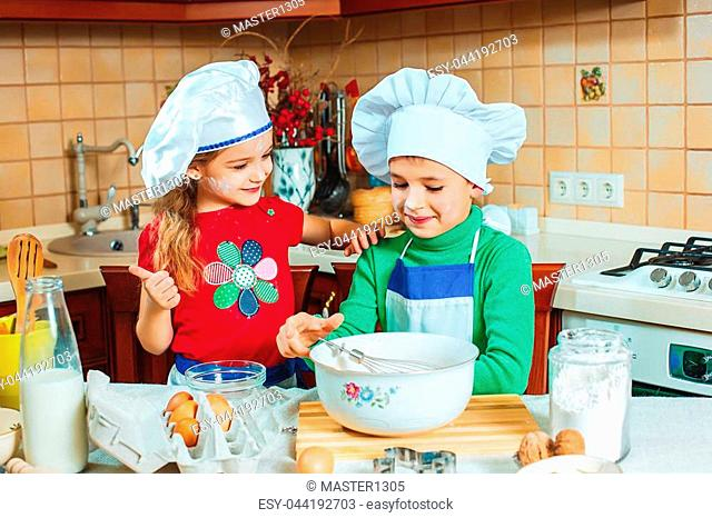 The happy two funny kids are preparing the dough, bake cookies in the kitchen