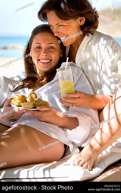 Mother and daughter with a snack on the beach