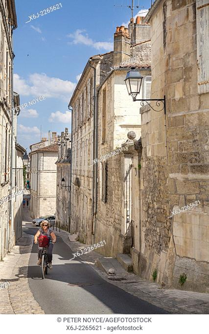 Woman cycling up the steep hill of Rue des Jacobins in Saintes
