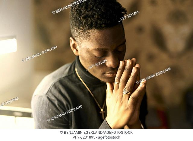 emotional man with closed eyes and folded hands, indoors at home, in Munich, Germany