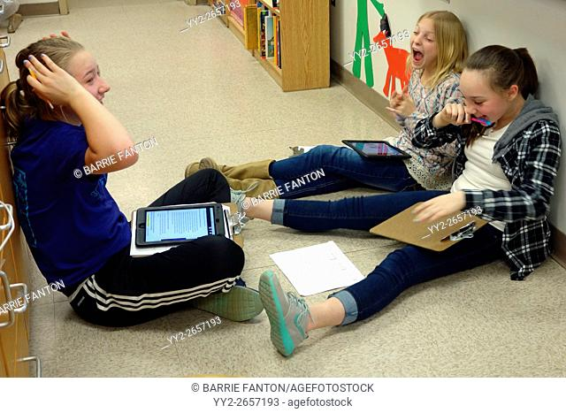 6th Grade Girls Laughing and Working Together on Science Project, Wellsville, New York, USA