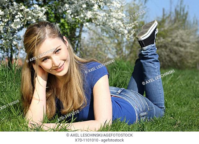 Portrait of young brunette woman lying on meadow
