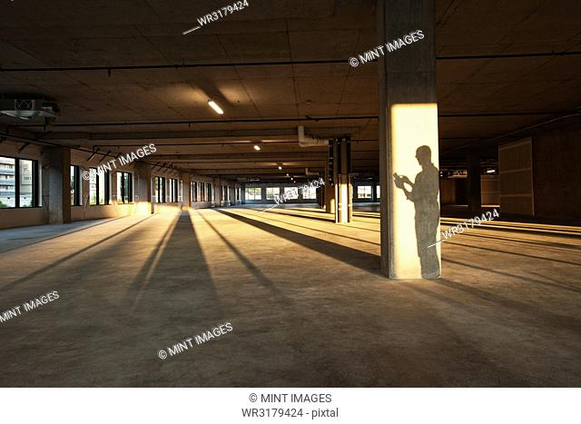 Shadow of a business man cast on a central post of a large empty raw office space