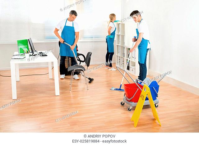 Group Of Three Janitors In Blue Apron Cleaning Office