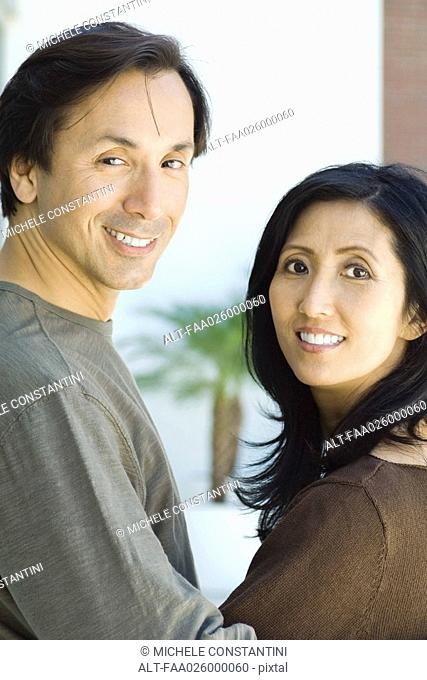 Couple smiling over their shoulders at camera, portrait