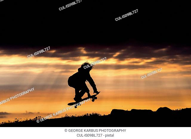 Young boy skateboarding at sunset, jumping, in mid air, Doolin, Clare, Ireland