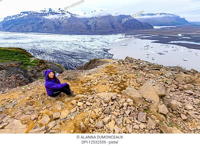 A female hiker in warm clothing poses on a mountain top overlooking the glacier lake and valley below at Vatnajokull National Park; Iceland