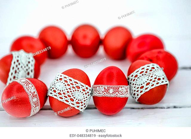 Red Easter eggs on white background tied lace tape , close-up , lying on a white wooden background still life