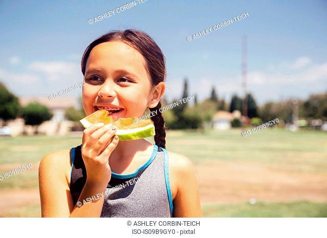 Schoolgirl eating melon slice on school sports field