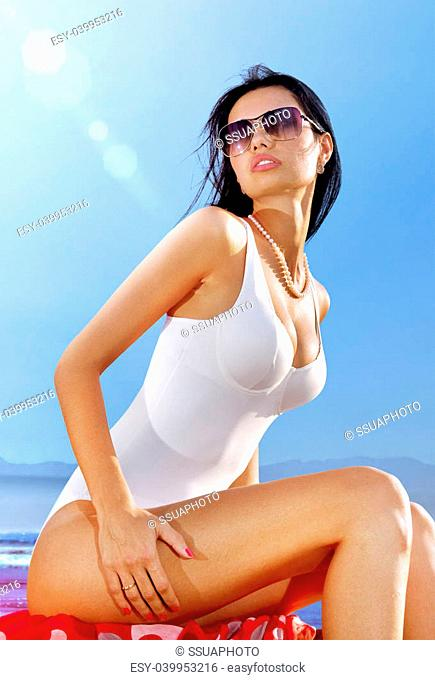 beautiful woman in white swimming suit sits on coast and takes sun bath