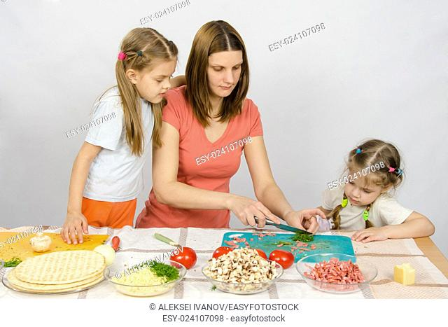 Two daughters are watching with interest as the mother chopped green